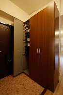 AFTER 大容量の縦型の玄関収納を設置。壁との隙間にはパイプを渡して傘も収納。