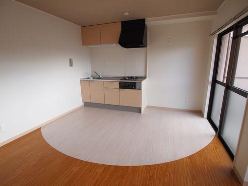 (写真 施工後)ウッディナチュラルタイプで仕上げたLDK キッチン部分とリビングの、フロアタイルを丸くカットして貼り分け、おしゃれな空間に