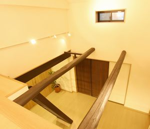 ロフトから見下ろしたリビング。キッチンの扉は古い建具を活用。 ※ツシとは、中2階などにある物置。古民家では主にカマドや風呂焚きに使うシバなどを置いていたらしい。