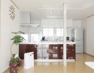 構造上抜けない柱はクロスを貼って空間のアクセントに。リビングからの太陽光でキッチンも明るい。