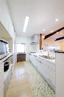 AFTER:手元が見えないセミオープンの対面型キッチン。収納力のあるカップボードを設置。