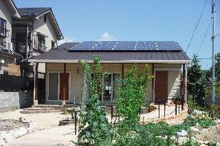 片流れの屋根を利用して太陽光パネルを設置。右手に玄関。左手ドアはトイレ。外のテラスから車椅子でも入れるようにしています。
