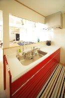 AFTER:コンパクトなキッチン、赤い色がナチュラルテイストの住まいのアクセントに。