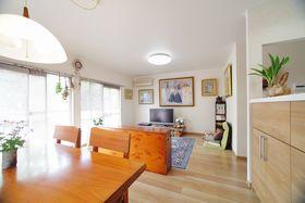 たくさんある絵画などが映えるように、清潔感のある白っぽいクロスと、明るい木目調の床材を選択。木のテーブルセットでぬくもりのあるリビングに。
