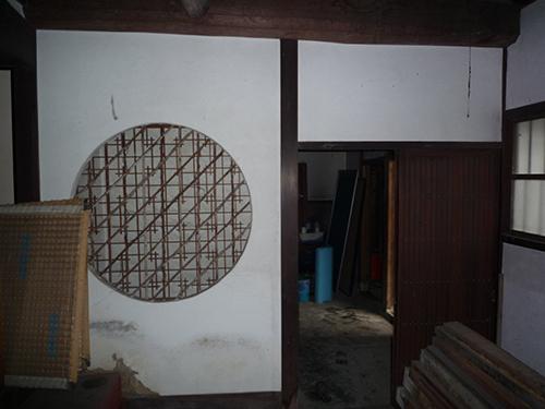 施工前 玄関から土間続きで奥の台所へ、仕切りの壁には格子の扉と、 丸くトリミングした明かり取りの窓には竹で細工された障子が入っています。