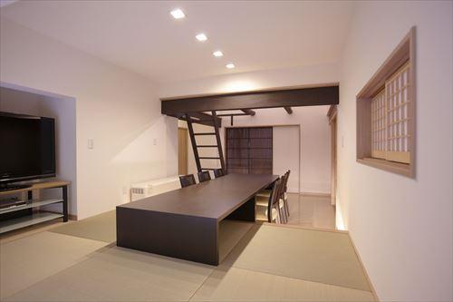 施工後のリビング 階段の上がロフト、 手前は畳コーナーにして、大きなテーブルを設置。右手の小窓の向こうは玄関